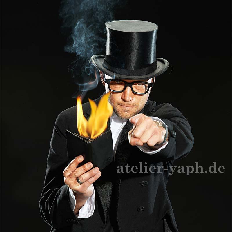 Fotos für Homepage und Businessportrait für einen Zauberer mit Zylinder und brennender Brieftasche aus dem Fotostudio Yaph in Trier