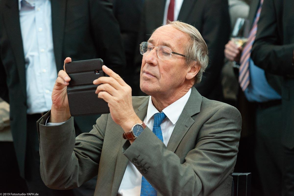 Herr beim Fotografieren mit seinem Smartphone porträtiert von Fotostudio Yaph Trier