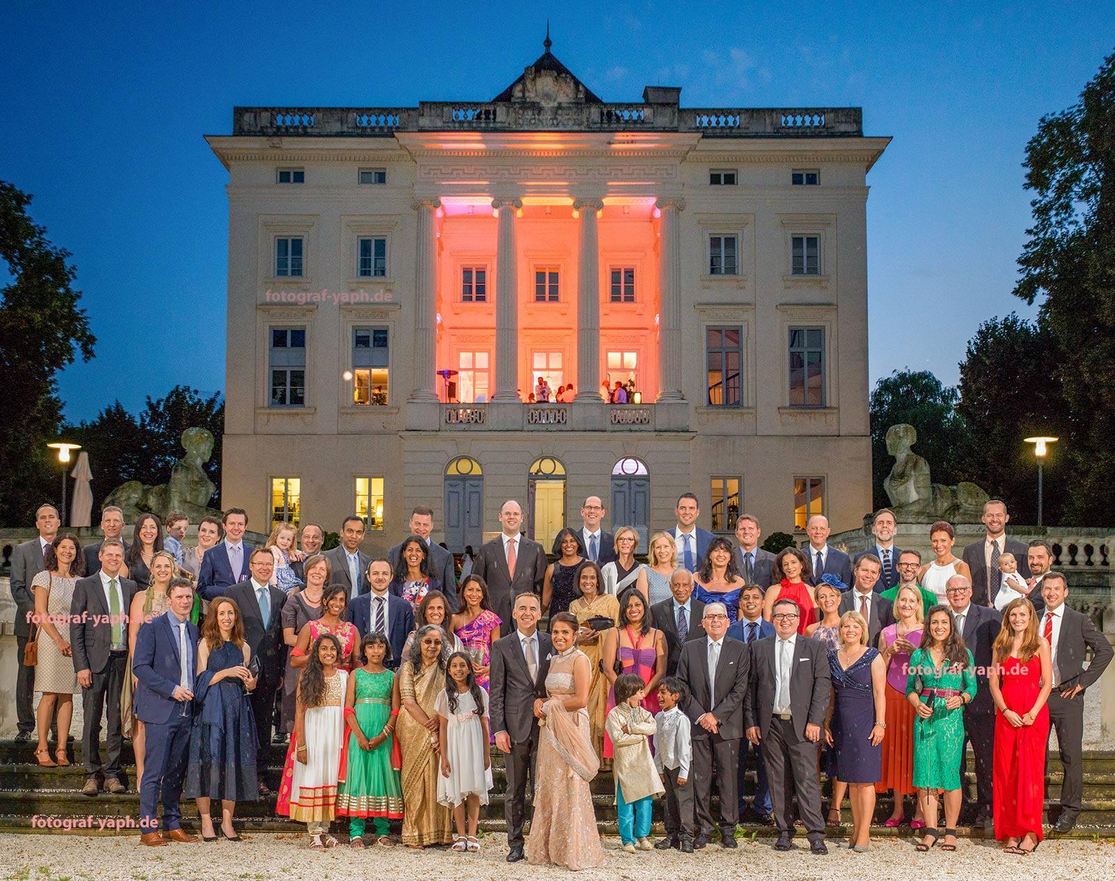 Fotograf für Hochzeiten Yaph präsentiert ein Gruppenfoto mit dem Brautpaar und der Hochzeitsgesellschaft vor dem Schloss Monaise in Trier.